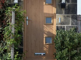 Close-up of bespoke composite door in Irish Oak.