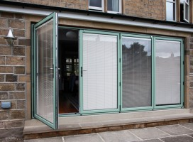 Aluminium bi-fold doors in Chartwell green with integral blinds, Newsome