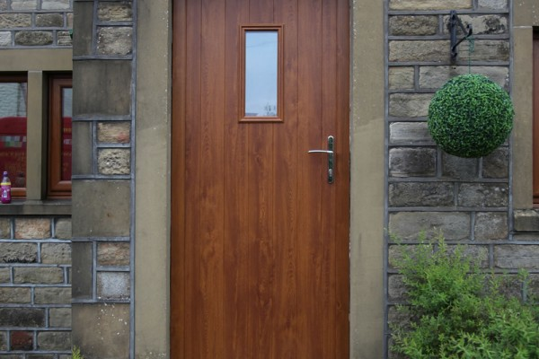 Flint composite door in Golden Oak shaped to fit aperture.